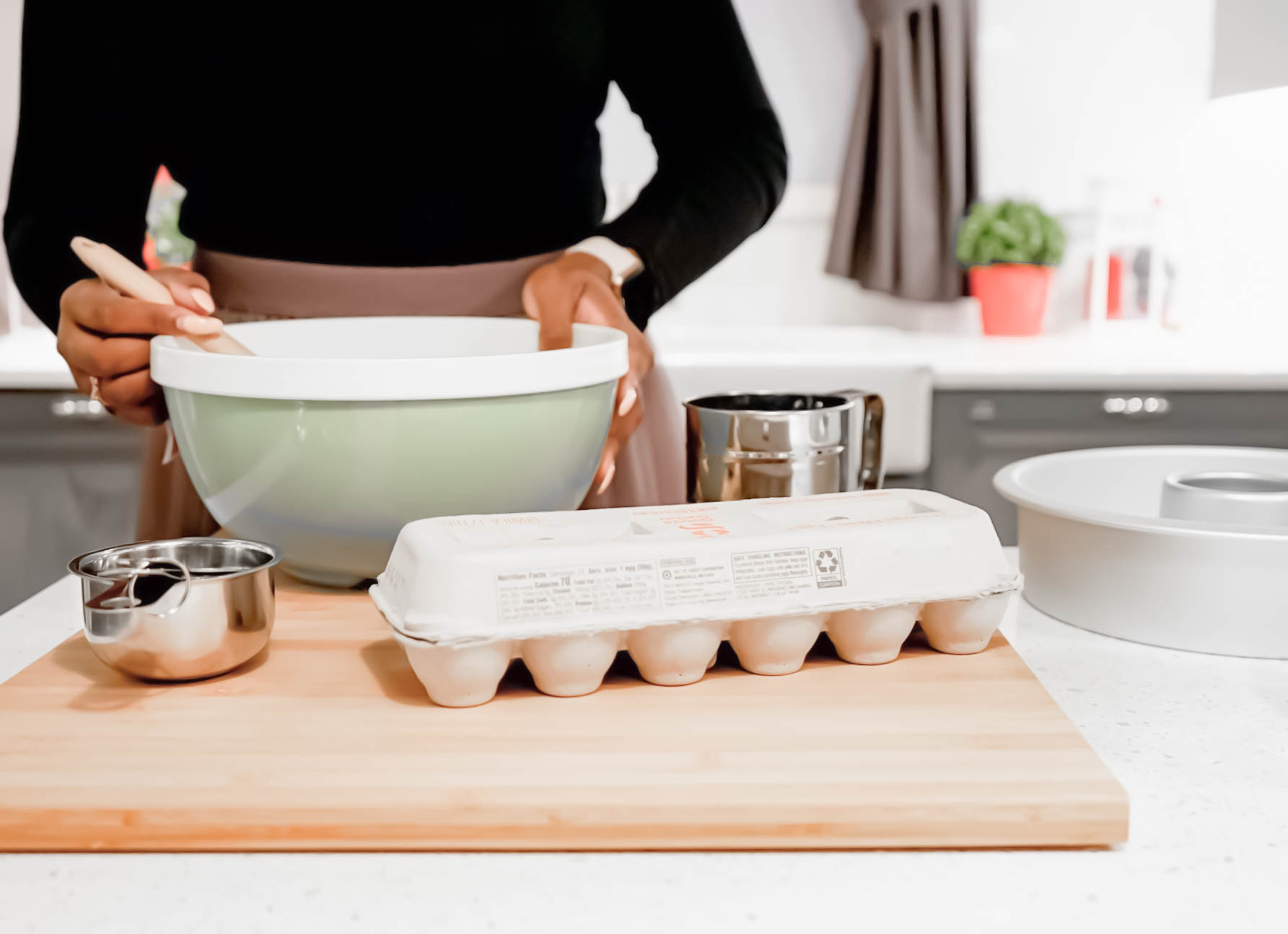 woman in the kitchen with a mixing bowl and baking ingredients